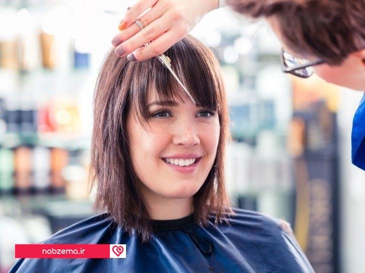 آرایشگر در حال کوتاه کردن مدل موی چتری