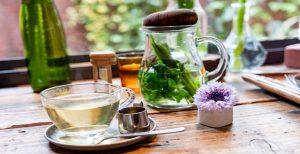 فنجان حاوی دمنوش زنجبیل به همراه قوری حاوی دمنوش و لوازم تزئینی دیگر روی میز چوبی