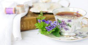 فنجان حاوی دمنوش خارمریم به همراه بوته تزئینی آن